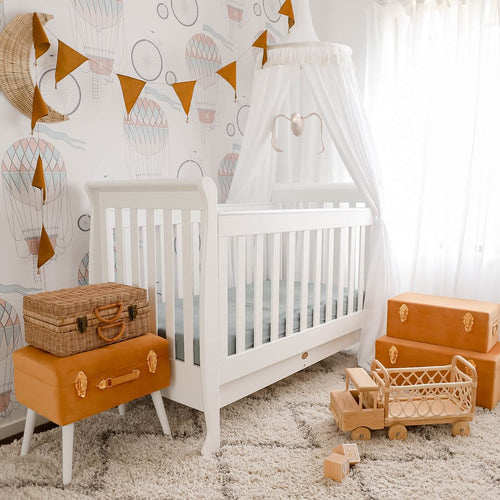 White round canopy hanging over white cot bed in nursery with mustard suitcase storage and mustard bunting with rattan toy truck on floor