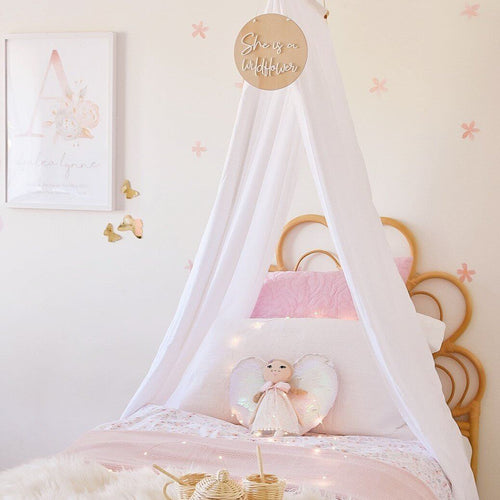 white drape canopy hanging above simngle bed in girls toddler bedroom with doll sitting on bed