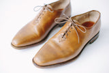 Top view of mens shoes in tobacco color, handmade with brown leather,mens brogues one piece of leather