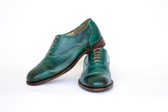 green oxford shoes with cap toe and brown laces