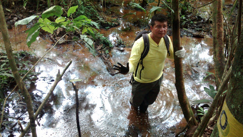 Donald Moncayo showing the petroleum pollution in a river downstream from an open oil pit