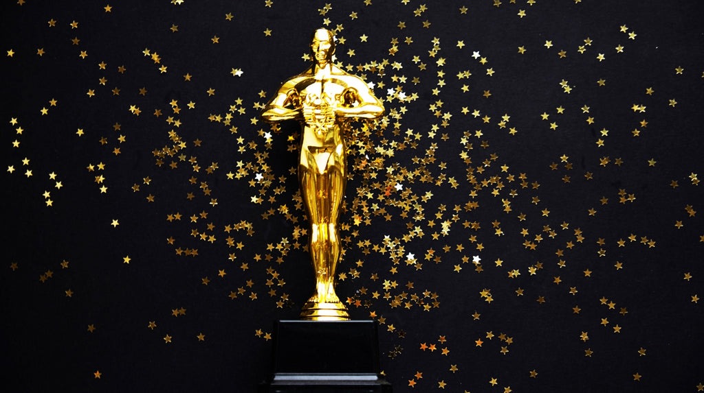 The Oscar surrounded by gold star confetti