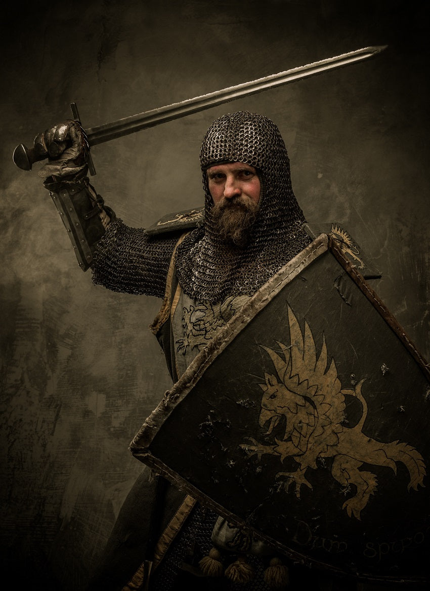 Bearded medieval knight in armor with sword and shield