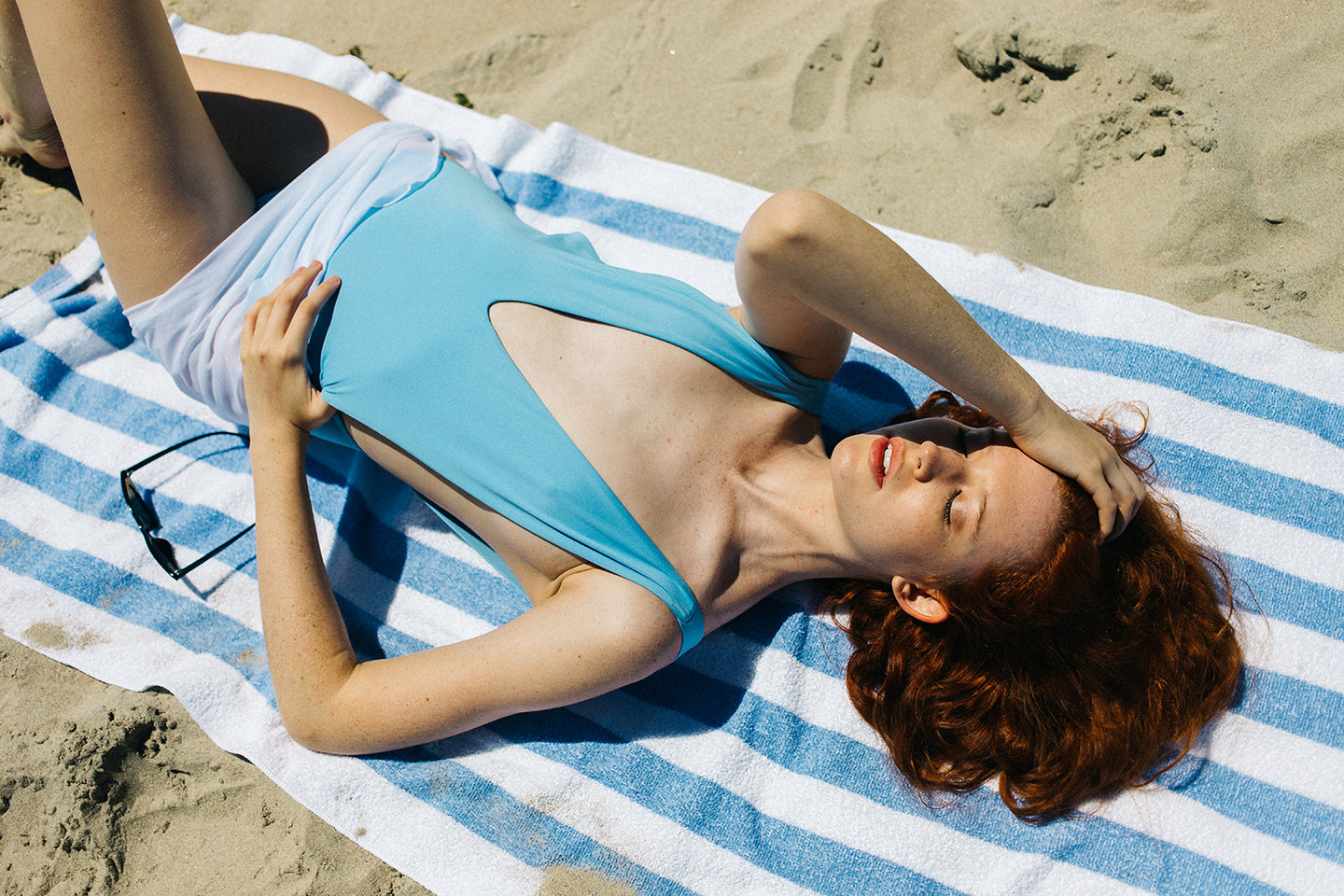 Woman in a blue one piece luxury swimsuit laying down on a beach towel