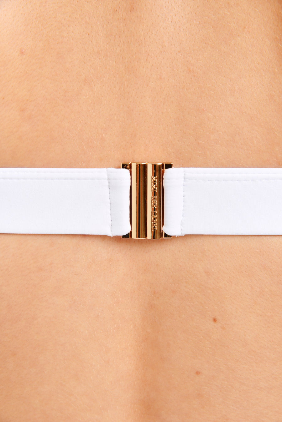 Close up of gold clasp on a white swimsuit top