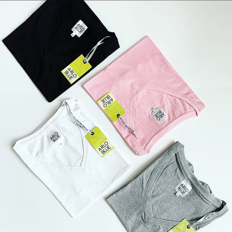 Four deep V-neck, short-sleeved T-shirts colored white, black, pink, and grey.