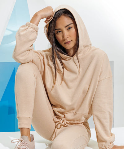 A lady sitting on white blocks with her arm resting on one raised knee. She is wearing an oversized cropped beige hoodie with matching sweatpants and sneakers.