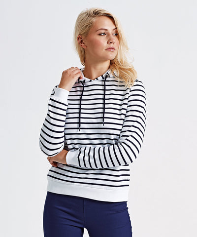 A young woman dressed in a black and white striped hoodie paired with fitted blue pants.