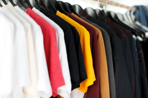 Multicolored short sleeve shirts hanging on a wooden rack.