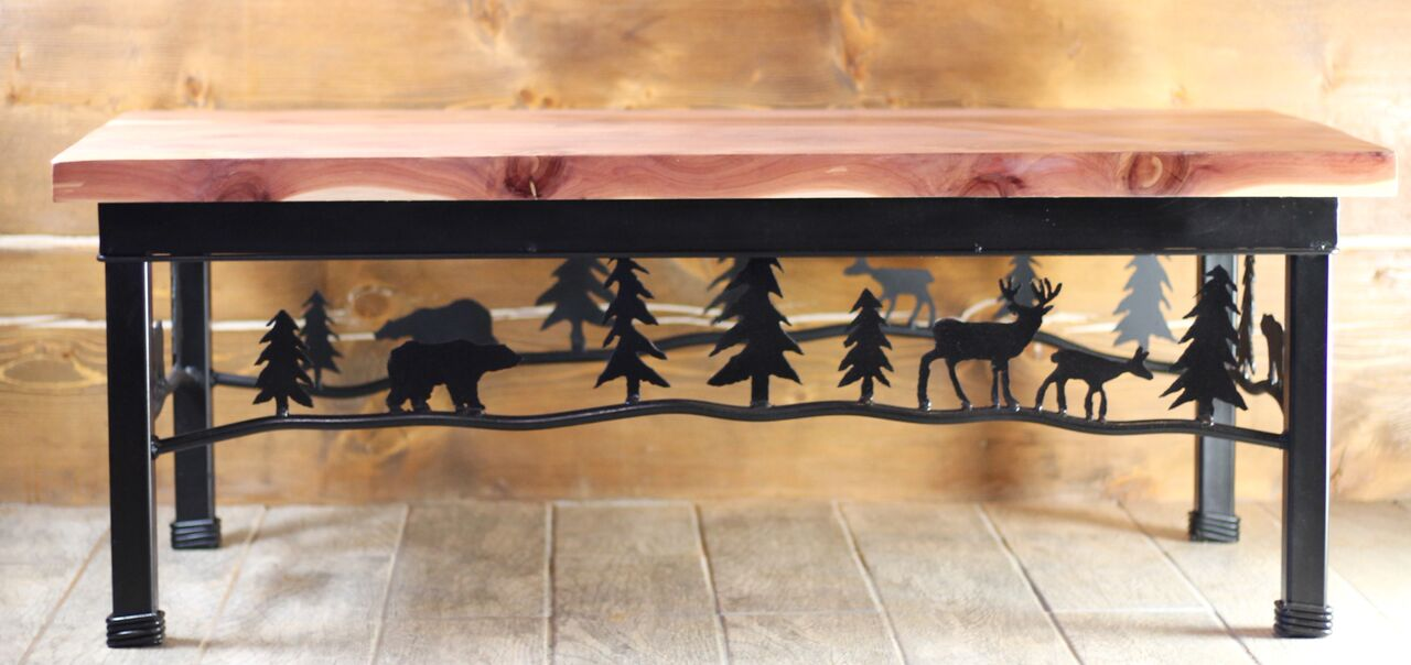 "Add a cozy cabin feel to any room with this unique wilderness coffee table. Metal base featuring a mountain scene of trees, bear and deer. Hand crafted metal and locally sourced cedar top.   Matching side tables also available in this collection.  Approximate size: 48"" x 24""  Black finish Hand Crafted in the USA RedRiverIron.com"