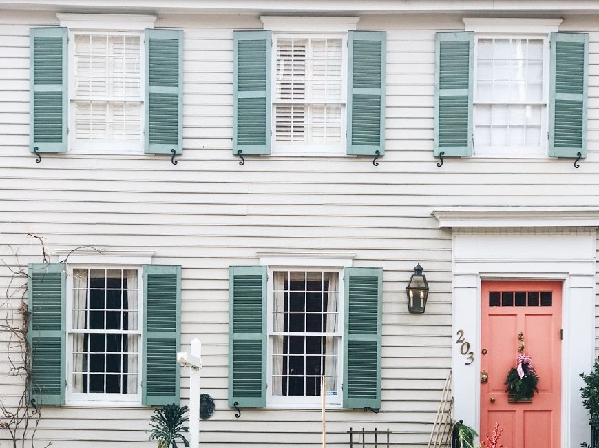 light grey house with teal shutters and a peach door