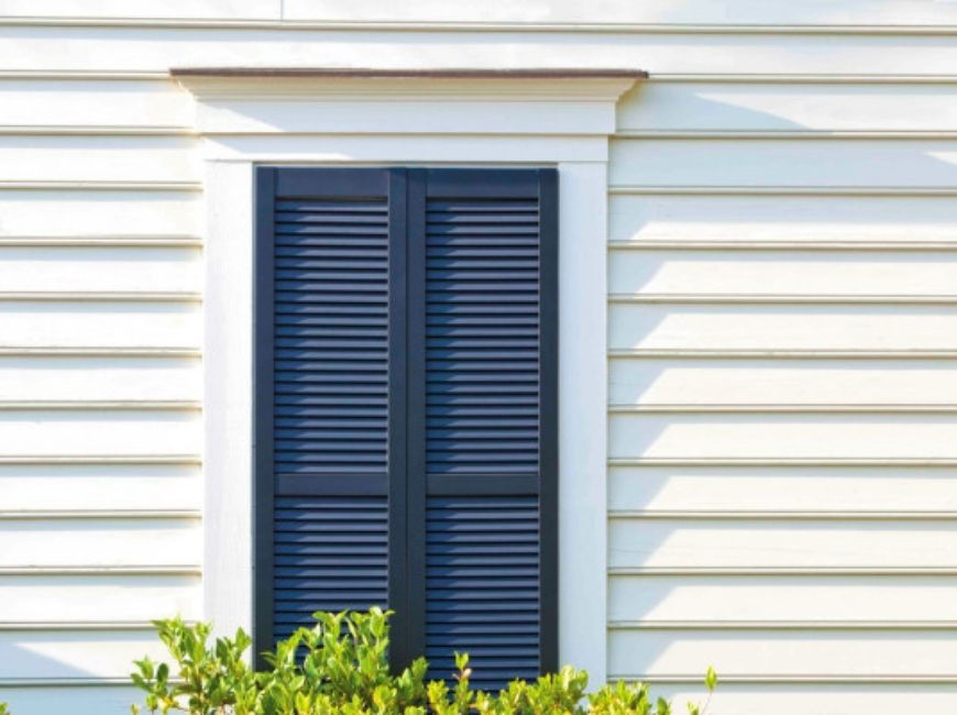 cream house with navy louvered shutters