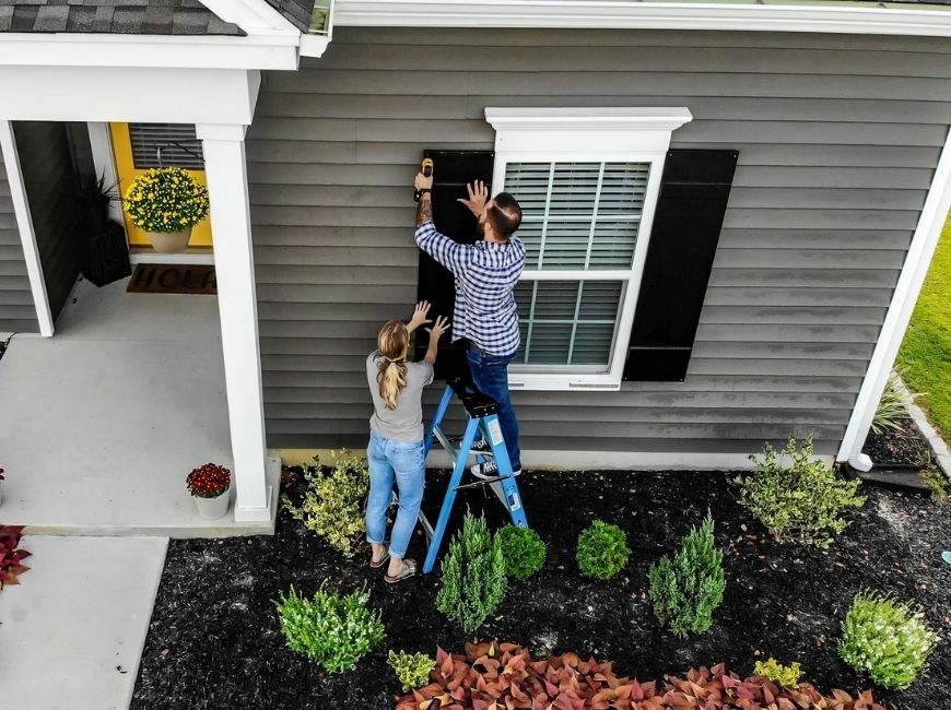 woman and man checking on black shutters on a grey house