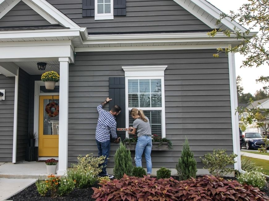 leveling black shutters on a grey home