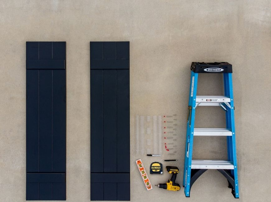 black shutters with ladder, measuring tape and tools