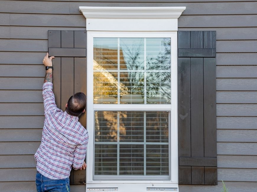 man replacing black shutters on a grey house