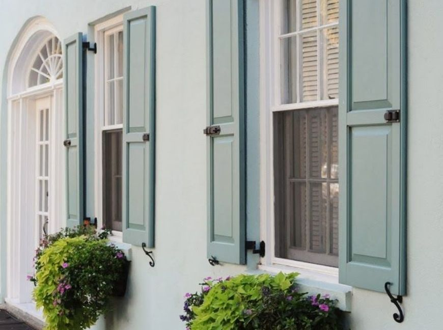 white house with blue/green shutters and window boxes
