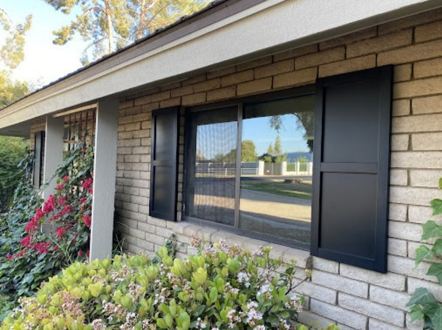 brick home with black flat panel shutters