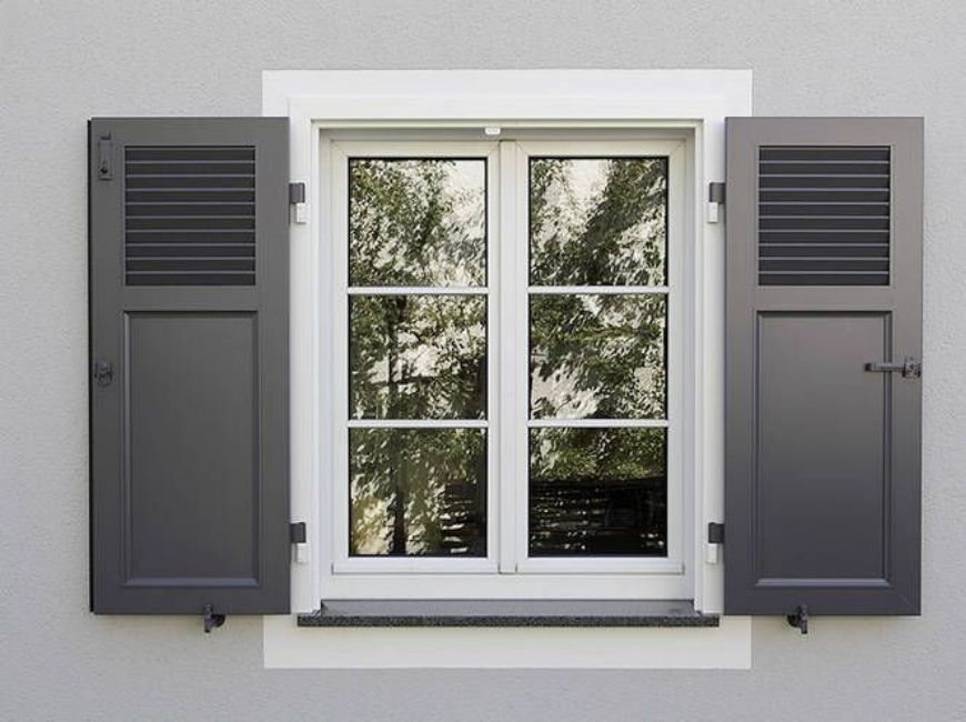 grey stucco home with black louvered over flat panel shutters
