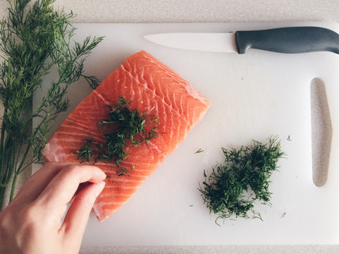 Fish on cutting board with greenery being sprinkled on top