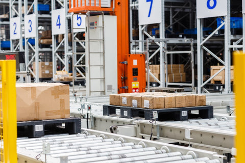 Conveyor belt in manufacturing warehouse with brown boxes on it