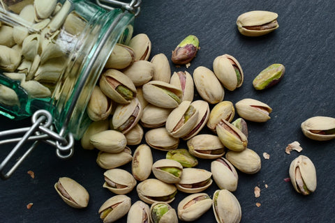 Pistachios being poured out of a jar