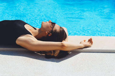 Woman on side of pool sun bathing with arms up