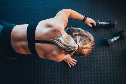 Above view of woman at gym reaching for dumbbells while kneeling on ground