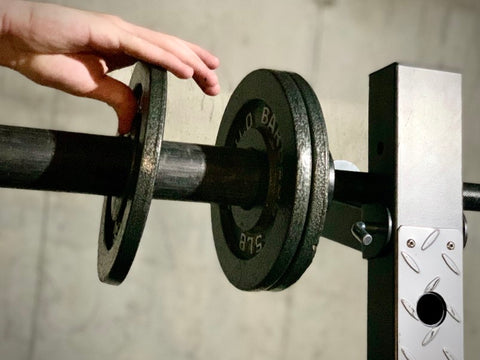 Close up of hands adding plates to lifting bar