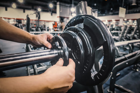 Hands adding plates to barbell