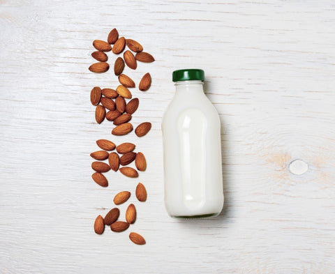 Jar of Almond Milk Next to Almonds on a Table