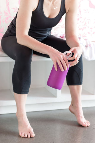 Woman in workout clothes drinking water.