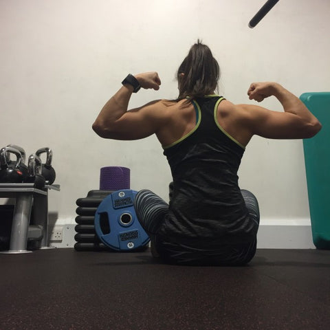 Back view of woman flexing muscles while sitting on gym floor