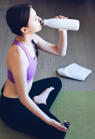 Woman drinking BCAA from a water bottle.