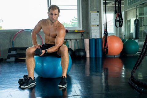 Man on yoga ball leaning on elbow while flexing in gym