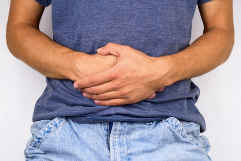 Man with hands in fist at lower stomach