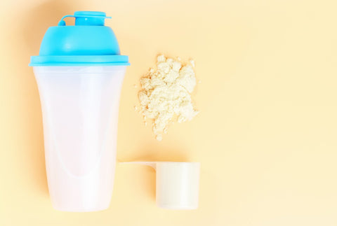 Protein bottle shaker with protein scoop and protein powder next to it