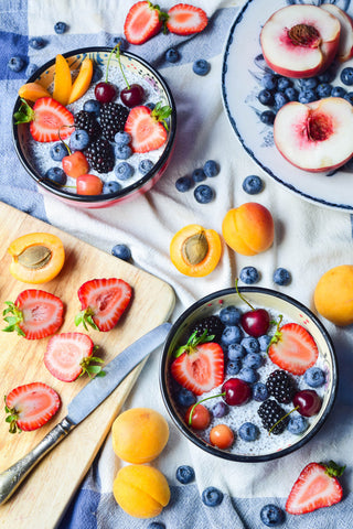 Bowls and trays full of strawberries, cherries, and blueberries