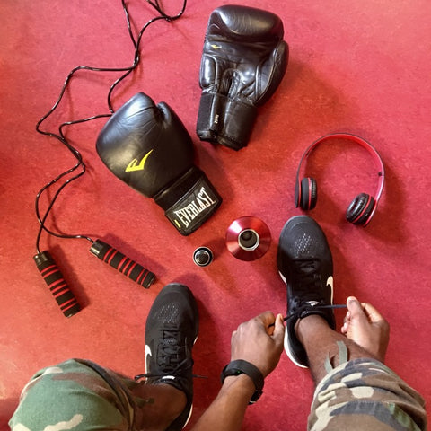 Man tying shoes next to boxing gloves, jumprope, and headphones on ground