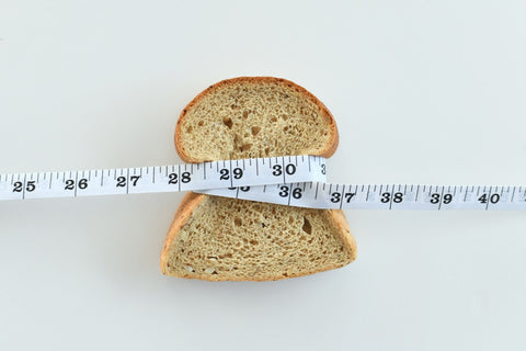 Piece of bread being squeezed by a tape measure