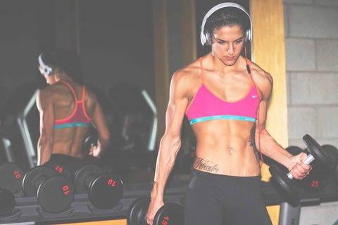 Woman looking down while lifting dumbbells in gym