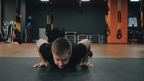 Man with elbows bent close to body in burpee position