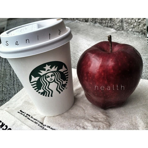 Starbucks coffee cup next to red apple