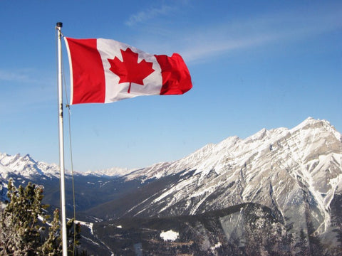 Canadian Flag over looking snowy Canadian mountains