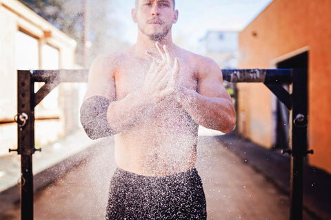 Man clapping hands with chalk in front of weight bar