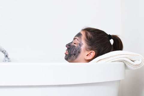 Side view of woman in bathtub with charcoal face mask on