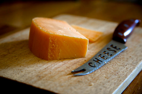 Cut block of cheddar cheese on cutting board next to knife