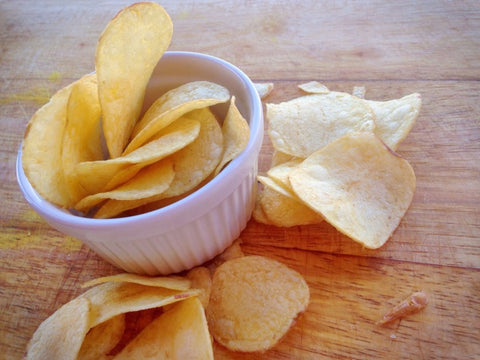 Small glass white bowl of chips overflowing
