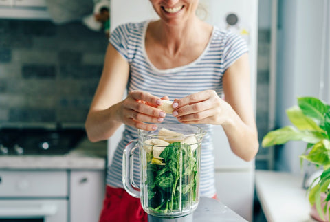 Woman making a spinach shake in the blender