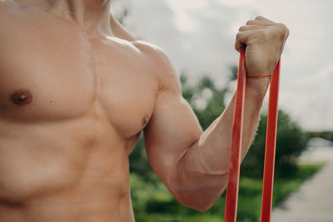 Man doing a curl with red resistance band